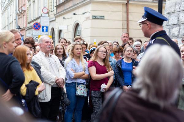 zdjęcie przedstawiające grupę ludzi słuchającą oprowadzającego